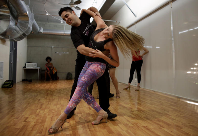 In this Monday, April 21, 2014 photo, Kendra Haynes, 26, of Miami, right, dances with Renato Medeiros, 33, of Brazil, during a Brazilian zouk dance class at the VK Dance Studio in North Miami Beach, Fla. Zouk dance and music, born in the French Caribbean, adopted in Brazil and spread through Latin America and Europe, is now taking root in the United States. Haynes is one of the first to give zouk classes in Miami. (AP Photo/Lynne Sladky)
