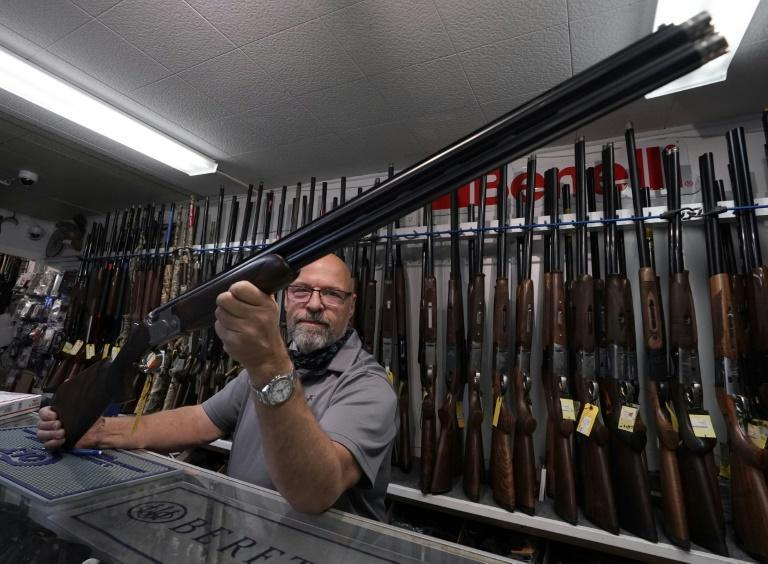 Salesman Paul Fraker shows off weapons for sale at Coliseum Gun Traders Ltd. in Uniondale, New York