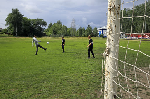 In this photo taken on Thursday, July 5, 2018, local boys play on the soccer pitch where Russian star midfielder Alexander Golovin practiced as a child, in Kaltan, Russia. When Russia plays at the World Cup, Kaltan looks like a ghost town. This remote Siberian coal-mining town is the home of Golovin, whose key role in Russia's run to the World Cup quarterfinals has made him a national hero. (AP Photo/Yaroslav Belyaev)