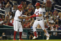 Washington Nationals' Luis Garcia, right, rounds the bases past interim third base coach Henry Blanco after hitting a solo home run in the seventh inning of a baseball game against the Philadelphia Phillies, Wednesday, Aug. 4, 2021, in Washington. (AP Photo/Patrick Semansky)