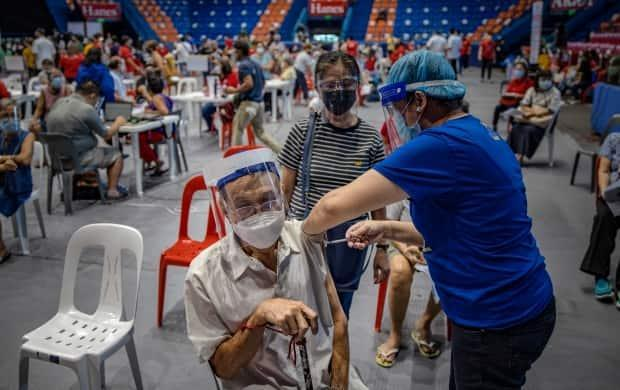 An elderly man is administered the AstraZeneca COVID-19 vaccine in San Juan, metro Manila, Philippines. Millions of people worldwide have received the vaccine.