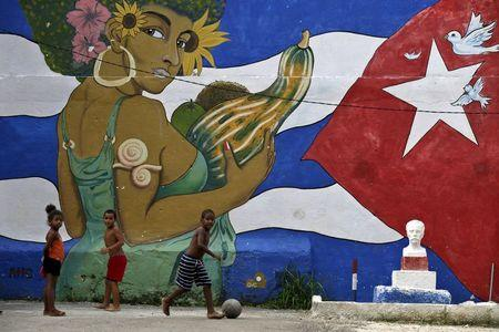 Children play soccer in front of graffiti depicting Cuba's national flag, in Havana
