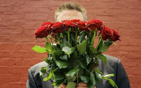 Man holding flowers - Credit: Getty Images