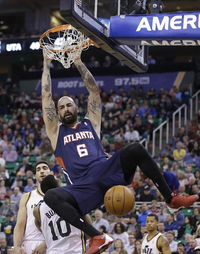 Atlanta Hawks' Pero Antic (6), of Macedonia, dunks the ball against Utah Jazz's Enes Kanter, rear, and Utah Jazz's Alec Burks (10) in the second quarter during an NBA basketball game Monday, March 10, 2014, in Salt Lake City. (AP Photo/Rick Bowmer)