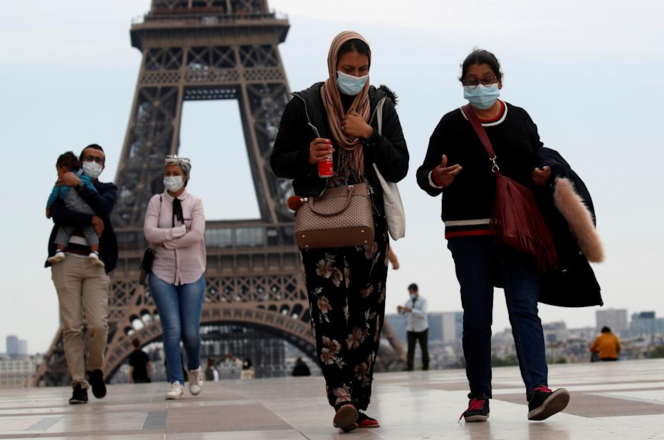 People wearing face masks walk at Trocadero square near the Eiffel Tower, as France began a gradual end to a nationwide lockdown due to COVID-19 in Paris, France, May 16, 2020. (REUTERS/Gonzalo Fuentes)