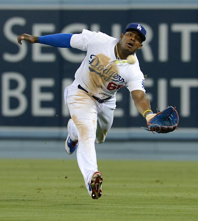 Los Angeles Dodgers' Yasiel Puig misses the ball as he reaches for a double hit by Arizona Diamondbacks' Martin Prado in the sixth inning of a baseball game Saturday, June 14, 2014, in Los Angeles. (AP Photo/Jayne Kamin-Oncea)