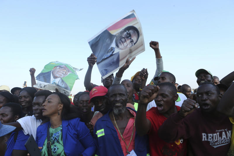 Supporters of Zimbabwe's former ruler, Robert Mugabe react upon the arrival of his remains at at RG Mugabe airport in Harare,Wednesday, Sept, 11, 2019.(AP Photo/Tsvangirayi Mukwazhi)