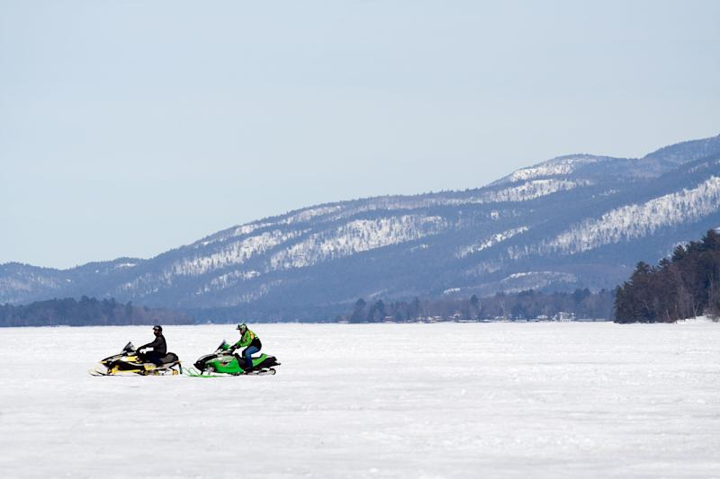 Snowmobilers make their way across a frozen Lake George in the Adirondacks.