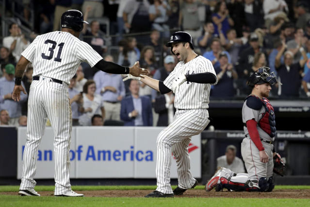 New York Yankees' Neil Walker, right, celebrates with Aaron Hicks (31) after hitting a three-run home run off Boston Red Sox relief pitcher Ryan Brasier during the seventh inning of a baseball game Tuesday, Sept. 18, 2018, in New York. Red Sox catcher Christian Vazquez is at right. (AP Photo/Julio Cortez)