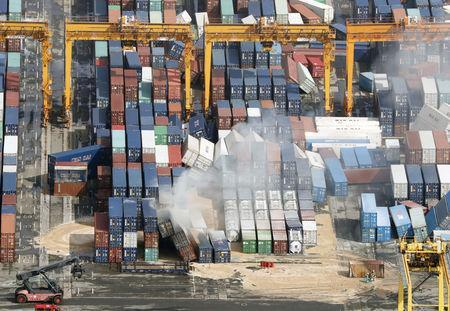 Smoke is seen among containers damaged by Typhoon Jebi, in Kobe, western Japan, in this photo taken by Kyodo September 5, 2018. Mandatory credit Kyodo/via REUTERS