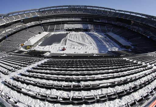 In this photograph taken with a fisheye lens, snow is accumulated on the seats and on the field of MetLife Stadium as crews removed snow ahead of Super Bowl XLVIII following a snow storm, Wednesday, Jan. 22, 2014, in East Rutherford, N.J. Super Bowl XLVIII, which will be played between the Denver Broncos and the Seattle Seahawks on Feb. 2, will be the first NFL title game held outdoors in a city where it snows. (AP Photo/Julio Cortez)