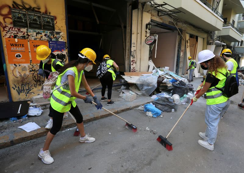 Volunteers clean debris from the street following Tuesday's blast in Beirut's port area
