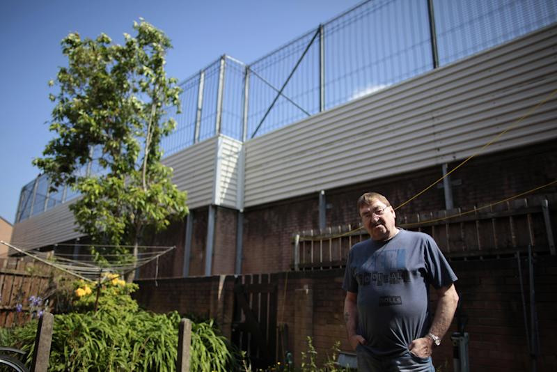 In this photo taken on June 10, 2013, James McDowell is dwarfed by a peace wall as he stands in his garden in the Catholic Short Strand area of East Belfast, Northern Ireland. The peace wall divides the Short Strand from the Protestant Cluan Place. When President Obama comes to Belfast, he's expected to praise a country at peace and call for walls that separate Irish Catholics and British Protestants to come tumbling down. Barely a 10-minute walk from where the U.S. leader is speaking Monday, June 17, 2013, those walls have kept growing in size and number throughout two decades of slow-blooming peace. Residents on both sides of the battlements today insist they must stay to keep violence at bay. (AP Photo/Peter Morrison)