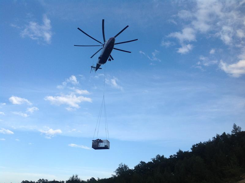 In this Saturday, Aug. 17, 2013 photo provided by the Russian Emergency Ministry, the Amur region branch, Emergency Ministry helicopter lifts a cage carrying a bear from a flooded Amur river in the Amur region in Riussia. The Russian Emergency Situations Ministry says around 20,000 people have been forced to leave their homes since July in the wake of floods in Russia's Far East. (AP Photo/ Russian Emergency Ministry, The Amur Region Branch)