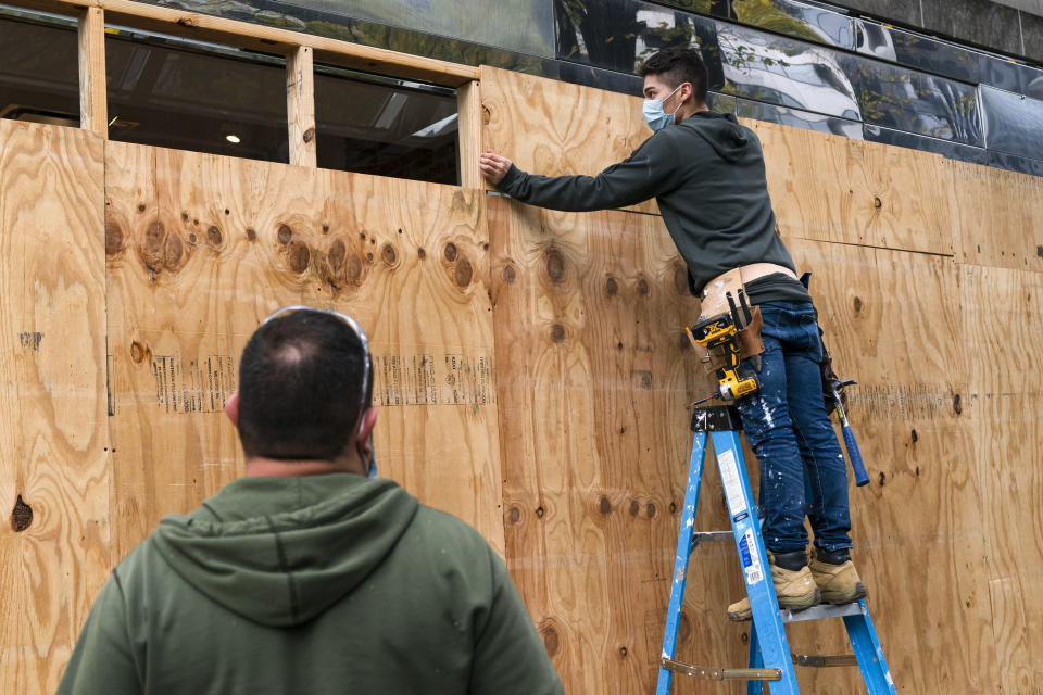 Ahead of the presidential election, workers board up a Pret A Manger restaurant along K Street NW, Friday, Oct. 30, 2020, in downtown Washington not far from the White House. (AP Photo/Jacquelyn Martin)