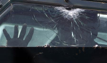 A government soldier inside an armoured vehicle peers out of a bulletproof window, which was damaged during a firefight with Muslim rebels from Moro National Liberation Front (MNLF), in a residential district in Zamboanga city in southern Philippines September 12, 2013. REUTERS/Erik De Castro