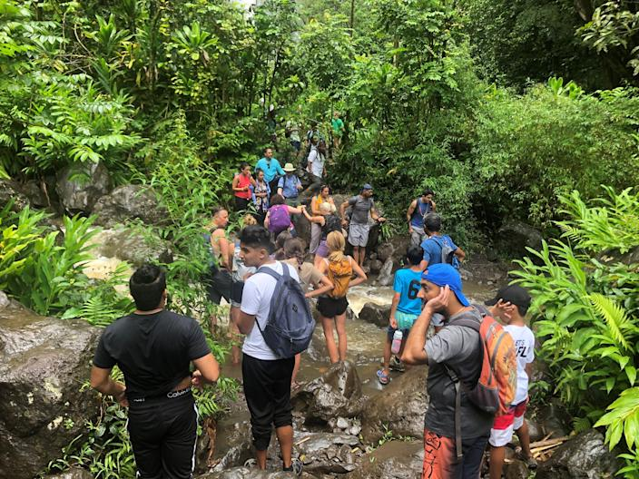 Hikers at the end of the Pipiwai Trail at Haleakala National Park on the Hawaiian island of Maui. The 4-mile roundtrip hike, which features a bamboo forest and the stunning Waimoku Falls waterfall, is at the end of the long road to Hana.