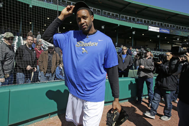 Followed by cameras former NBA All-Star Tracy McGrady removes his cap after a pitching workout at the Sugar Land Skeeters baseball stadium Wednesday, Feb. 12, 2014, in Sugar Land, Texas. McGrady hopes to try out as a pitcher for the independent Atlantic League Skeeters. (AP Photo/Pat Sullivan)