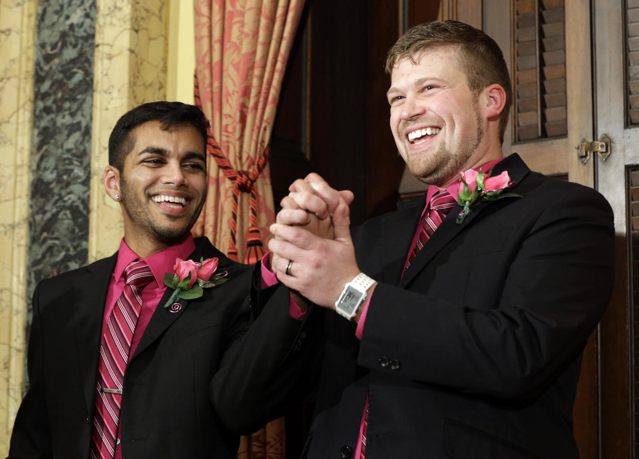 Shehan Welihinda, left, and Ryan Wilson react after participating in a marriage ceremony at City Hall in Baltimore, Tuesday, Jan. 1, 2013. Same-sex couples in Maryland are now legally permitted to marry under a new law that went into effect after midnight on Tuesday. Maryland is the first state south of the Mason-Dixon Line to approve same-sex marriage. (AP Photo/Patrick Semansky)