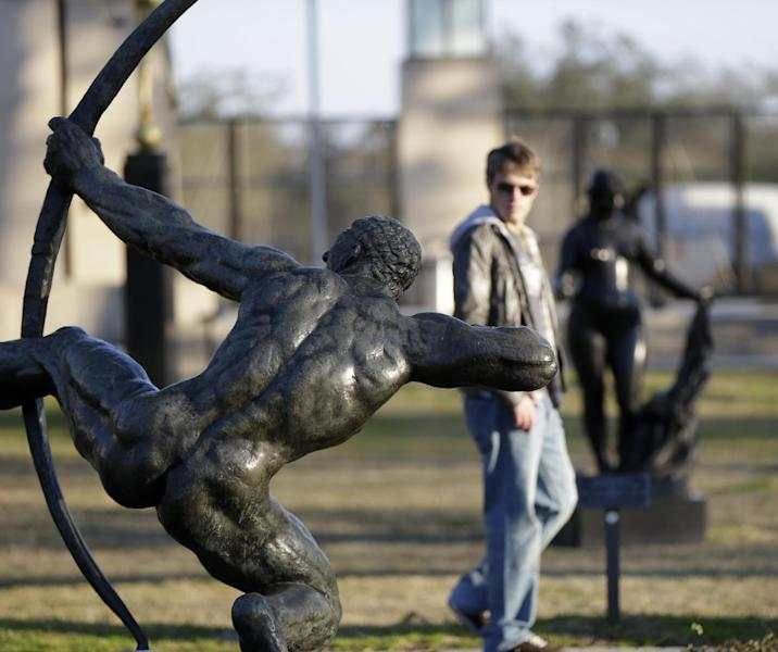 People walk through the Sydney Walda Besthoff Sculpture Garden in City Park in New Orleans, Tuesday, Jan. 15, 2013. The New Orleans Museum of Art is located in the park, and while there's a fee to enter the museum, just beyond the museum are dozens of art objects you can see for free in the Sydney and Walda Besthoff Sculpture Garden. The sculptures, valued at more than $25 million, can be viewed in a relaxing setting that includes meandering footpaths, pedestrian bridges and reflecting lagoons. (AP Photo/Gerald Herbert)