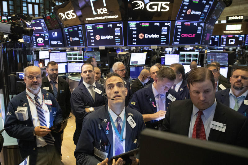 FILE - In this Sept. 18, 2019, file photo traders at the New York Stock Exchange follow stock prices just before the Federal Reserve made its interest rate announcement. Investors hit the brakes on a hard-charging market over the last two quarters as the U.S.-China trade war created an uncertain economic path forward. (AP Photo/Mark Lennihan, File)
