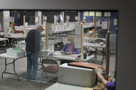 County employees process mail-in ballots at a Clark County election department facility Saturday, Oct. 31, 2020, in Las Vegas. (AP Photo/John Locher)