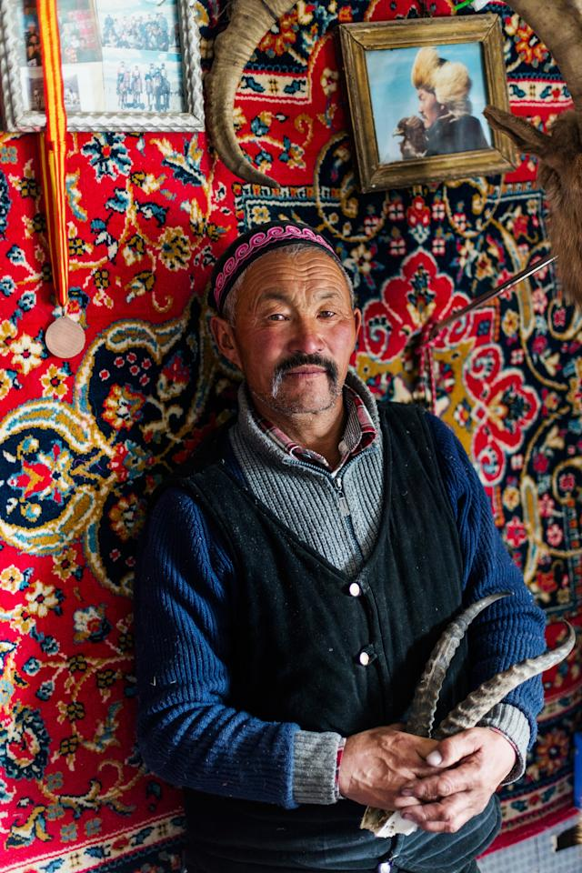 """This portrait of Dalaikhan was taken inside his permanent winter home, where he lives with his wife, son, and daughter. His nickname, ağası, means big brother in Kazakh. A lot of the eagle hunters that we traveled with look up to him—he's their leader in a way. He's also very involved with the eagle festival and wants to revive the tradition of eagle hunting, which is dying out because less and less of the younger generation want to do it. There are portraits of Dalaikhan with his eagle, like the one hanging in the top right corner, all throughout the house."""