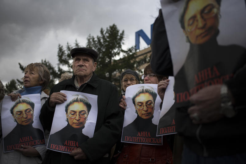 People rally, holding portraits of slain journalist Anna Politkovskaya, in downtown Moscow, Sunday, Oct. 7, 2012. About 200 people rallied Thursday on the 6th anniversary of the killing of Anna Politkovskaya, calling on the authorities to find and punish the killers of journalists and human rights activists in Russia. (AP Photo/Alexander Zemlianichenko)