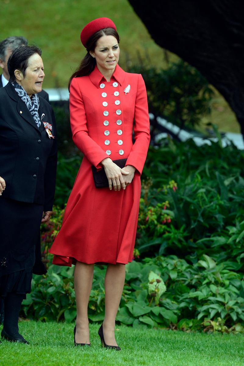 Kate channeled Princess Diana in a red military-esque Catherine Walker coat while arriving in New Zealand on April 7, 2014.