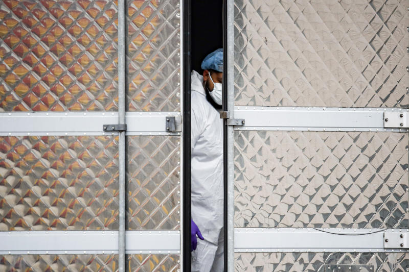 A medical worker wearing personal protective equipment due to COVID-19 concerns works inside a refrigerated container truck functioning as a makeshift morgue, Tuesday, March 31, 2020, at Brooklyn Hospital Center in the Brooklyn borough of New York. The new coronavirus causes mild or moderate symptoms for most people, but for some, especially older adults and people with existing health problems, it can cause more severe illness or death. (AP Photo/John Minchillo)