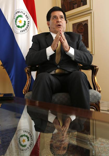 Paraguay's President Horacio Cartes talks during an interview at the presidential residence Mburuvicha Roga in Asuncion, Paraguay, Wednesday, Sept. 18, 2013. During the interview Cartes condemned tax evaders, said he'll require corporate partners to fund Paraguay's social development and took credit for Paraguay's first tax on commodities. This new 10 percent tax on soy, corn, wheat and sunflower profits falls far short of what he initially pushed for, but it's still expected to generate $300 million a year by 2015. (AP Photo/Jorge Saenz)