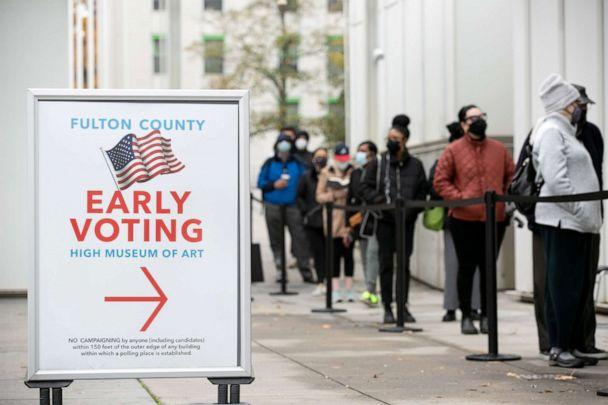 PHOTO: Voters line up for the first day of early voting outside of the High Museum polling station in Atlanta, Dec 14, 2020. (Jessica Mcgowan/Getty Images)
