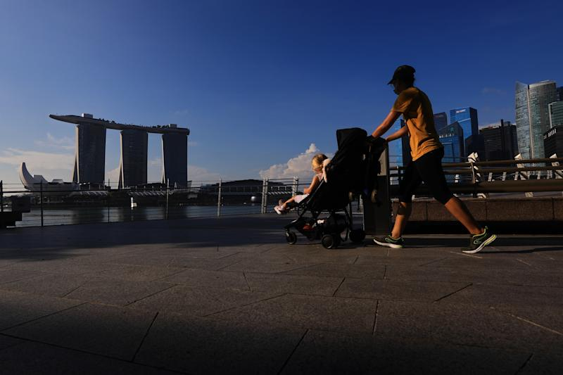 SINGAPORE - MAY 26: A woman wearing protective mask pushes a stroller with the Marina Bay Sands, ArtScience museum and the central business district pictured in the background on May 26, 2020 in Singapore. Singapore is set to ease the partial lockdown measures against the coronavirus (COVID-19) pandemic after 1 June in three phases to resume activities safely after it sees a decline in the new infection cases in the community. Singapore's gross domestic product (GDP) is expected to shrink as much as 7 percent this year as the country battles the slump in global trade and travel amid the coronavirus pandemic, according to the government report in the local media today. (Photo by Suhaimi Abdullah/Getty Images)