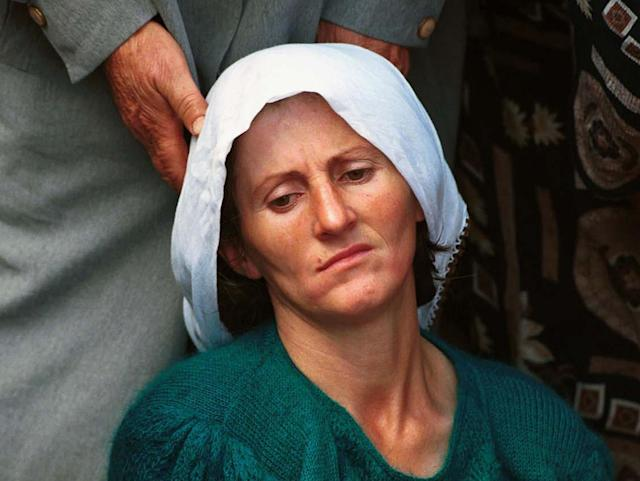 <p>An ethnic Albanian woman is supported as she mourns at the funeral of 34 KLA soldiers killed in a spring 1999 offensive against the Yugoslav Army at a mass funeral in Ferizaj, south of the Kosovo's capital, Pristina, on Sept. 12, 1999. (Photo: Jacqueline Larma/AP) </p>