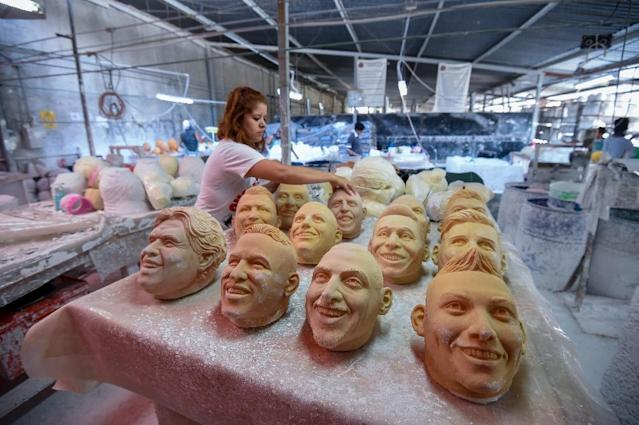 A worker arranges latex masks of football players at a factory in Jiutepec, Morelos State, Mexico (AFP Photo/ALFREDO ESTRELLA)