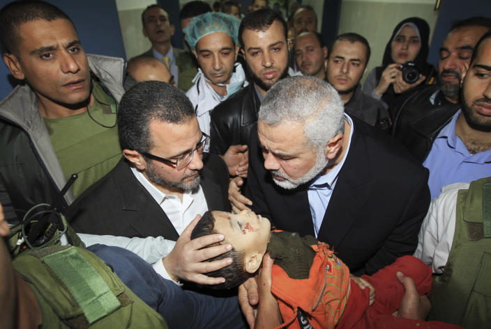 Gaza's Hamas Prime Minister Ismail Haniyeh, right, and Egyptian Prime Minister Hesham Kandil, left, hold the body of a Palestinian boy they claim was killed in an Israeli strike on Gaza City, as they show the body to the media at Shifa hospital in Gaza City, Friday, Nov. 16, 2012. Neighbors said the boy was killed in a blast around 8:30 a.m. Friday, around the time Kandil was entering the territory. Israel, which ordinarily confirms strikes, vociferously denied carrying out any form of attack in the area since the previous night. (AP Photo/Mahmud Hams, Pool)