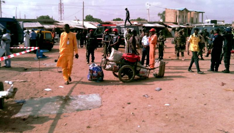 People and security personnel stand at the scene of a blast in the northern Nigerian city of Kano, on July 24, 2014