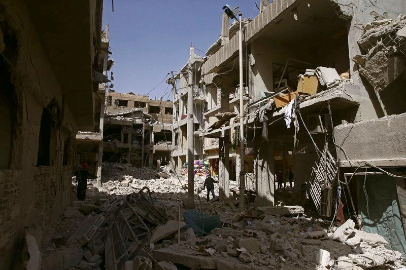 A man walks on rubble of damaged buildings in the besieged town of Douma