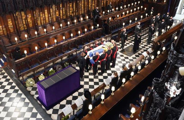 The Queen watches as pallbearers carry the coffin of the Duke of Edinburgh during his funeral at St George's Chapel, Windsor Castle, Berkshire