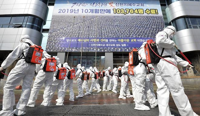 Soldiers in protective suits spray disinfectant to prevent the spread of the coronavirus in front of a branch of the Shincheonji Church of Jesus in Daegu, South Korea in March. Photo: Newsis via AP