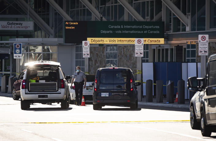 A Royal Canadian Mounted Police officer works at the scene as screens block off an area of the sidewalk after a shooting outside the international departures terminal at Vancouver International Airport, in Richmond, British Columbia, Sunday, May 9, 2021. (Darryl Dyck/The Canadian Press via AP)