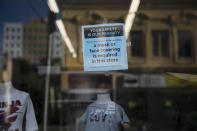 A sign requiring face masks is posted on the window of a clothing store during the coronavirus pandemic in the Westlake neighborhood of Los Angeles, Thursday, May 21, 2020. While most of California took another step forward to partly reopen in time for Memorial Day weekend, Los Angeles County didn't join the party because the number of coronavirus cases has grown at a pace that leaves it unable to meet even the new, relaxed state standards for allowing additional businesses and recreational activities. (AP Photo/Jae C. Hong)