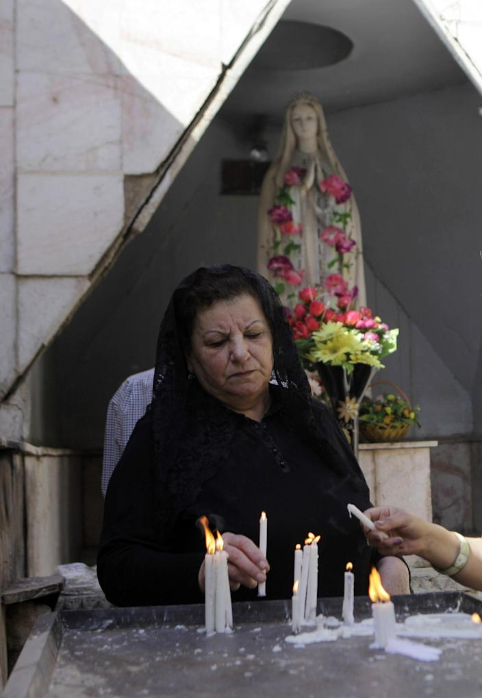 Iraqi Christians light candles before Easter mass at Virgin Mary Chaldean Church in Baghdad, Iraq, Sunday, March 31, 2013. The Chaldean Church is an Eastern Rite church affiliated with the Roman Catholic Church. (AP Photo/ Khalid Mohammed)