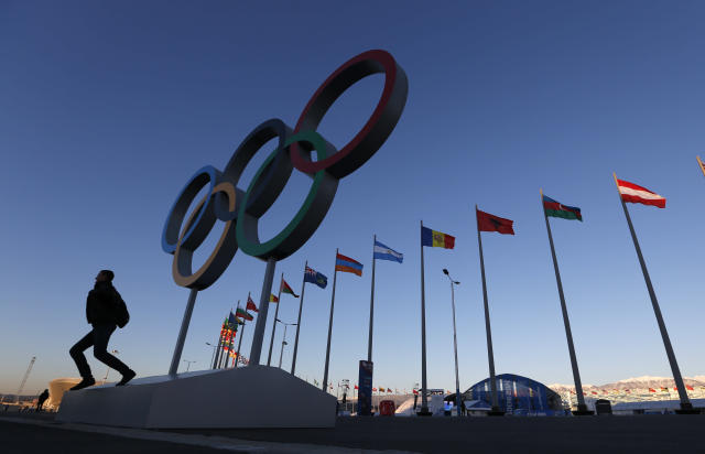 A man poses for a photo beneath the Olympic rings at Olympic Park, prior to the 2014 Winter Olympics, Monday, Feb. 3, 2014, in Sochi, Russia. (AP Photo/Robert F. Bukaty)