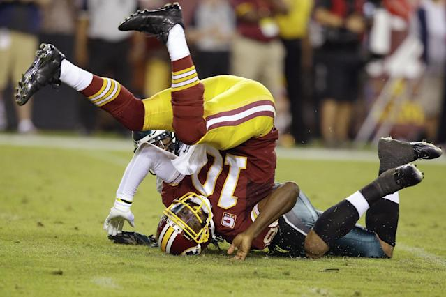 Washington Redskins quarterback Robert Griffin III rolls onto his head after he is tackled by Philadelphia Eagles outside linebacker Mychal Kendricks during the first half of an NFL football game in Landover, Md., Monday, Sept. 9, 2013. (AP Photo/Alex Brandon)
