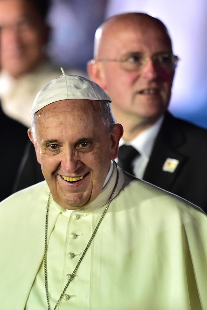 Pope Francis smiles, flanked by Head of Vatican Security Domenico Giani, as he arrives at a military airbase in Manila on January 15, 2015 (AFP Photo/Giuseppe Cacace)