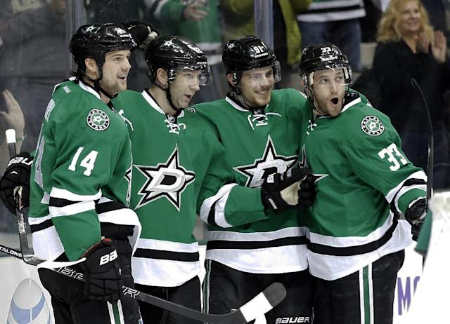 Dallas Stars' Jamie Benn (14), from left, Erik Cole, Tyler Seguin, and Alex Goligoski (33) celebrate a goal by Cole 14-seconds into the first period of an NHL Hockey game against the Edmonton Oilers, Tuesday, Jan. 14, 2014, in Dallas. (AP Photo/Tony Gutierrez)