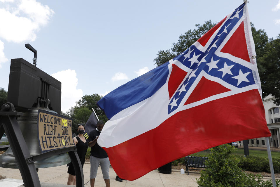 """A Mississippi state flag waves adjacent to a flag change supporter's sign that welcomes the state to """"the right side of history,"""" outside the Capitol in Jackson, Miss., Sunday, June 28, 2020, while lawmakers are expected to consider state flag change legislation. Mississippi Governor Tate Reeves has already said he would sign whatever flag bill the Legislature decides on. (AP Photo/Rogelio V. Solis)"""