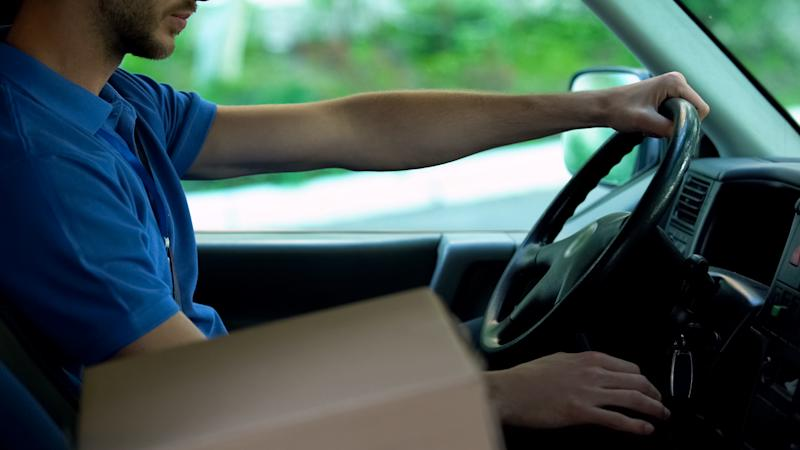 Mailman driving car, cardboard box standing near him, parcels express delivery
