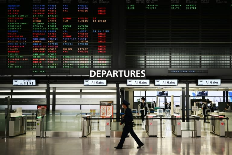 """A security guard walks past a signboard showing cancelled flights at the international departures area of Narita International Airport in Narita, Japan -- Prime Minister Shinzo Abe said the country's hospitals face a """"critical situation"""""""